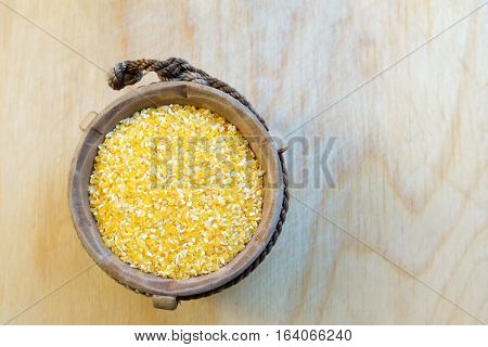 Close up view of corn groat in wooden pot