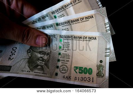 Person holding the new indian Rs 500 note isolated on black. These new currency notes have been recently authorized by the government