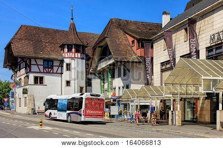 Aarau, Switzerland - 7 July, 2016: people, buildings and a bus on an old town street. Aarau is a town and municipality in Switzerland, it is the capital of the Swiss Canton of Aargau.