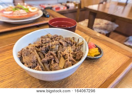 Butadon pork bowl is a Japanese dish consisting of a bowl of rice topped with pork simmered in a mildly sweet sauce