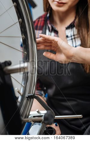 Checking the measurements of the wheel. Skillful beautiful feminine mechanic standing in the garage and holding the caliper while measuring the external and internal dimensions of the wheel