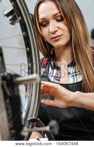 External and internal dimensions. Concentrated young feminine craftswoman standing in the workshop and holding the caliper while measuring the external and internal dimensions of the wheel