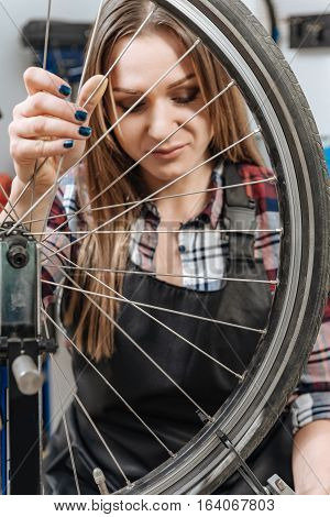 Repairing my bicycle. Positive delighted female technician standing in the workshop and repairing the wheel of the bicycle while expressing positivity