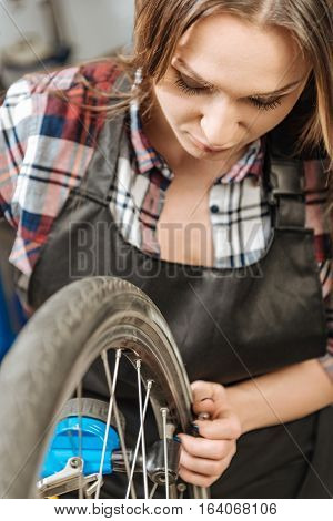 Measuring the pressure of tires on the vehicle. Mindful involved female technician sitting in the garage and holding the wheel of the bicycle while measuring the pressure of tires