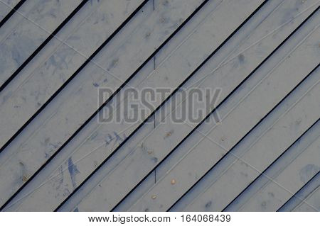 Pale blue rustic structured wall with diagonal lines.