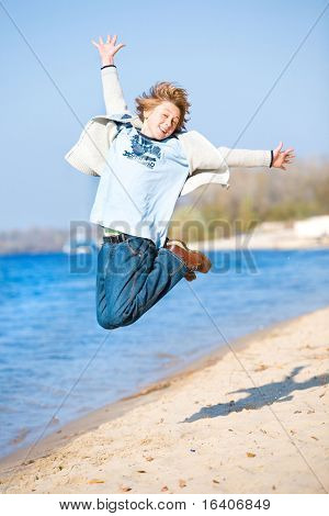 Happy jumping boy on beach