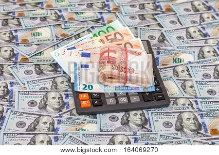 Folded stack of russian roubles euro banknotes and calculator on dollars background