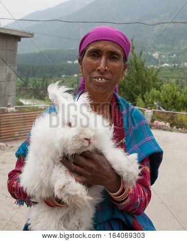 DHARAMSALA, INDIA. 2 Jun 2009: Rural residents in daily life. Hindu Woman with a white rabbit on hands. Western Himalayas, Himachal Pradesh, district of Kangra.