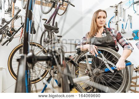 Masterful craftswoman working. Delighted athletic confident craftswoman standing in the repair shop and working while fixing the bicycle and holding different tools