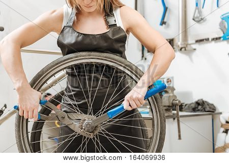 Strong craftswoman repairing the bicycle. Muscular athletic hardworking worker standing in the workshop and working while dismantling the chain of the bicycle and holding different tools