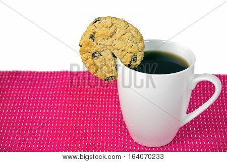 oatmeal cookie with raisins on rim of white cup and black coffee