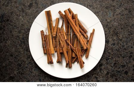 Cinnamon Sticks And White Plate On Countertop