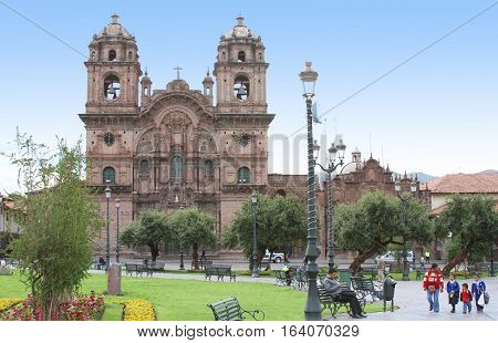 Cusco Peru - December 14 2016: Church of the Society of Jesus with landscaping and people on Plaza de Armas in Cusco Peru on December 14 2016