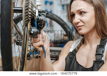 Delighted from my job. Cheerful smiling skillful craftswoman standing in the repair shop and working while fixing the chain of the bicycle