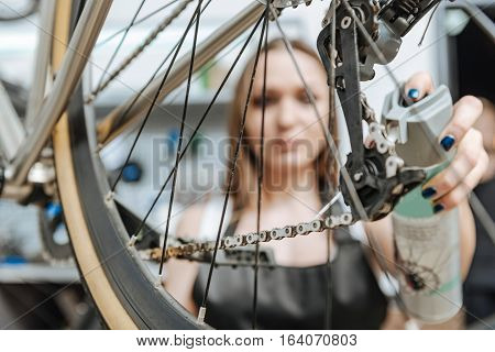 Fixing the chain. Young serious skillful craftswoman standing in the workshop near the bicycle and working while fixing the chain