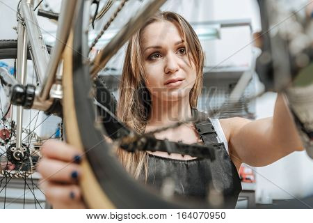 Checking each element. Muscular serious masterful craftswoman standing in the workshop near the bicycle and working while repairing it