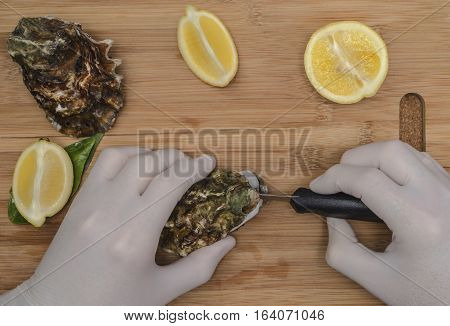 A man in rubber gloves preparation fresh oysters with a blade