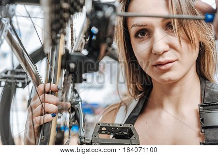 Attentive to details. Athletic mindful skilled master standing in the workshop near the bicycle and working while repairing it and holding the screwdriver