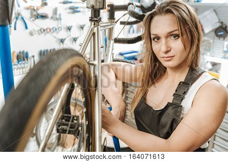 Time for rest. Delighted athletic positive craftswoman standing in the repair shop and resting while touching the bicycle and expressing her confidence