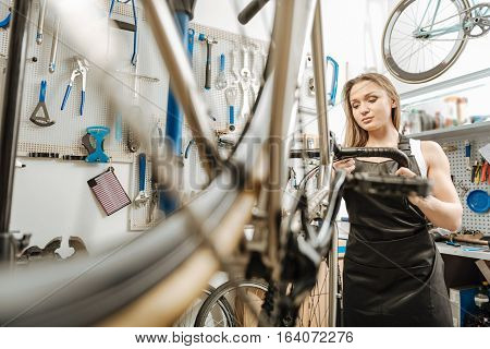 Attentive to details. Involved observant charming mechanic standing in the garage and working while fixing the bicycle