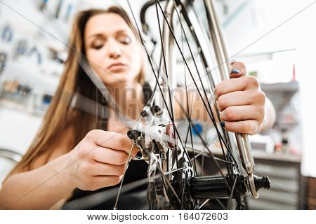 Pretty athletic involved technician standing in the repair shop and working while mending the bicycle