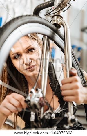 Overhauling the bicycle . Charming athletic female technician standing in the workshop and working while overhauling the mountain bicycle