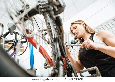 Full of interest. Watchful muscular young worker standing in the garage and working while repairing the bicycle and expressing concentration