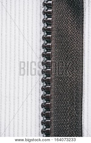 Milky white corduroy combined with dark brown zipper. Macro view