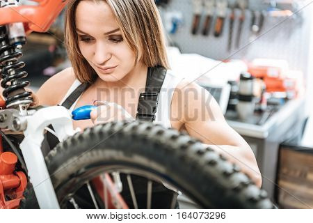 Involved in the process of repairing. Delighted athletic concentrated mechanic standing in the garage and working while repairing the bicycle and expressing happiness