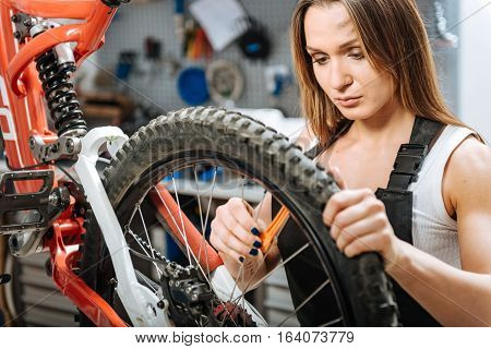 Woman doing male job. Involved athletic hardworking technician standing in the garage and working while repairing the bicycle and holding the wheel