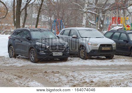 SARANSK, RUSSIA - JANUARY 1, 2017: Black Hyundai Santa Fe and silver Mitsubishi ASX on parking lot.