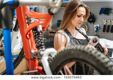 Full of delight. Hardworking positive smiling craftswoman standing in the garage and working while repairing the bicycle and holding instruments