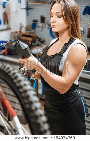 Weighting as the stage of process. Involved diligent attentive worker standing in the workshop and working while repairing the mountain bicycle and weighting all details.