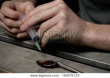 Caucasian teen boy filling an empty syringe with illegal drugs