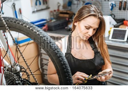 Attentive to details. Involved persevering female mechanic standing in the repair shop and working while repairing the bicycle and wiping the fuel oil