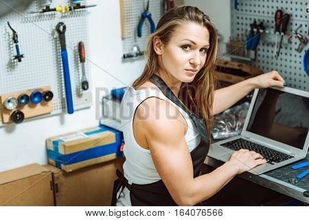 Doing my work. Beautiful athletic young craftswoman sitting in the garage and expressing confidence while using the laptop and having