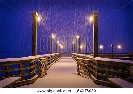 Winter Snow, Fishing Pier, Richmond, BC. A snow storm blankets a fishing pier on the bank of the Fraser River near Steveston at twilight. Richmond, British Columbia, Canada.