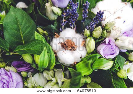 Delicate white ball cotton flower. Details of a bohemian bouquet of flowers. Winter floral composition, green background.