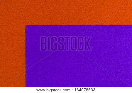 Eva foam ethylene vinyl acetate dark purple surface on orange sponge plush background