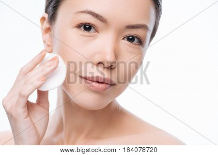 Pretty cheerful asian woman pressing a cotton pad to her cheek and cleaning her face while caring about skin