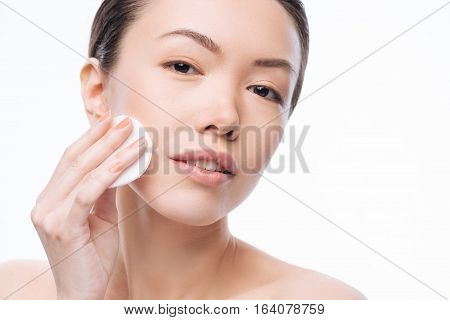 Caring about beauty. Positive pleasant young woman holding a cotton pad and cleaning her face with it while having her daily skin care routine