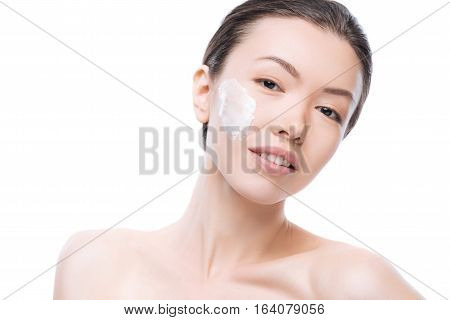 Cosmetic products. Joyful attractive young woman standing against the while background and having some facial cream on her cheek while smiling