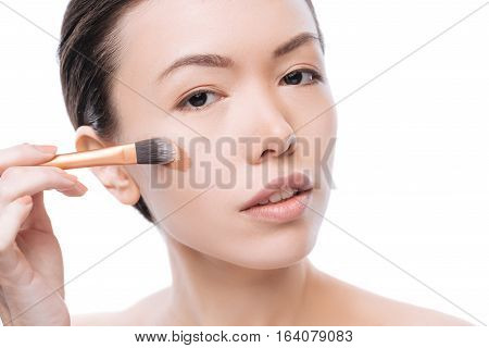 Perfect skin tone. Positive beautiful asian woman holding a cosmetic brush and making her skin tone perfect while applying make up