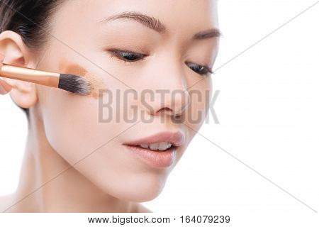 Foundation make up. Nice attractive asian woman applying several layers of liquid foundation on the cheek and looking down while holding a make up brush