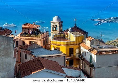 View from Castelmola Sicily: the bell tower in the light of the morning sun and 2 cruise ships in the sea.