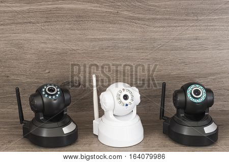 Three surveillance cameras, two black and one white