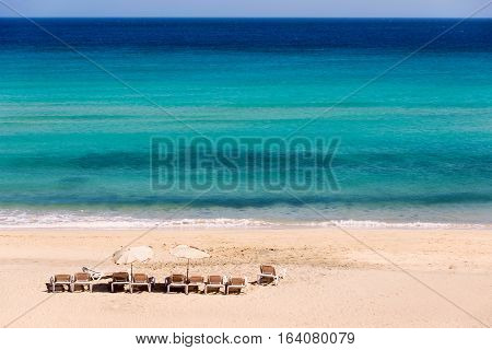 Sunbeds on an empty beach in Sicily
