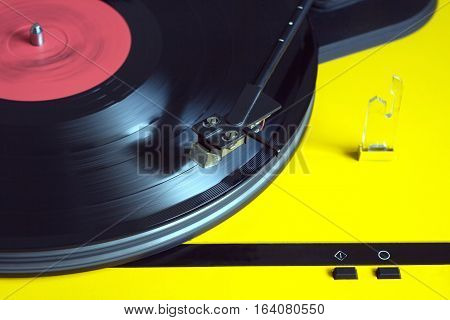 Turntable in yellow case playing a vinyl record with red label. Horizontal photo top view closeup