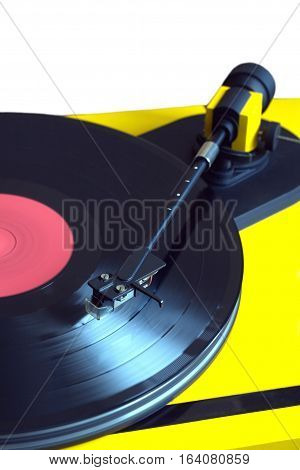 Turntable in yellow case playing a vinyl record with red label. Vertical photo isolated on white background closeup