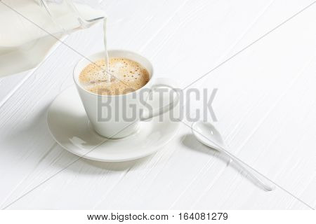 Cup Of Hot Cappuccino Coffee On A White Wood Table. Milk Being Poured Into A Cup Of Coffee. Adding M